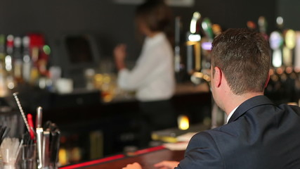 Businessman ordering whiskey in a classy bar