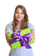 Frau überreicht Geschenk mit lila Schleife