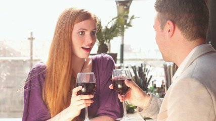 Loving couple talking while having glass of red wine