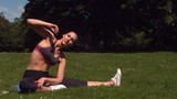 Sporty brunette stretching on grass