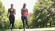 Two young girls jogging in a park