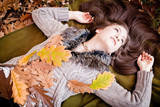 Beautiful woman  lying on autumn leaves in park