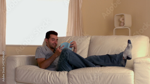 Attractive man jumping on couch with book
