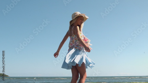Attractive blonde with straw hat spinning on the beach