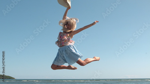Attractive blonde holding straw hat jumping on the beach