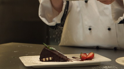 Chef giving a cake the finishing touch