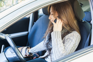Woman in car,talking to mobile phone and searching purse