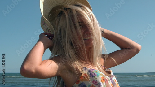Attractive blonde turning with straw hat on beach