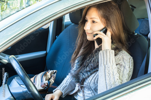 Woman in car calling by mobile phone