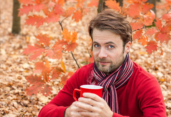Man drinking hot tea outdoor in a park while autumn picnic
