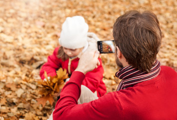 Father photograph his girl child playing in an autumn park