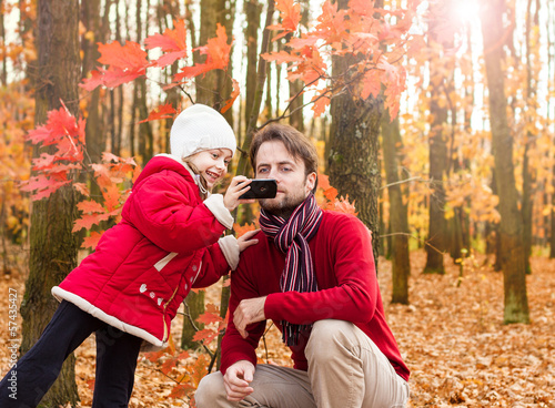 Girl child and father taking autumn photo with mobile phone