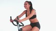 Sporty cheerful brunette using exercise bike