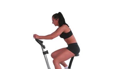 Tone brunette spinning on exercise bike