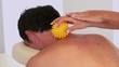 Masseuse using yellow massage ball on clients neck