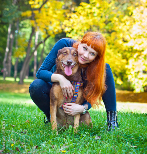 Elegant woman has fun with her big dog in the park