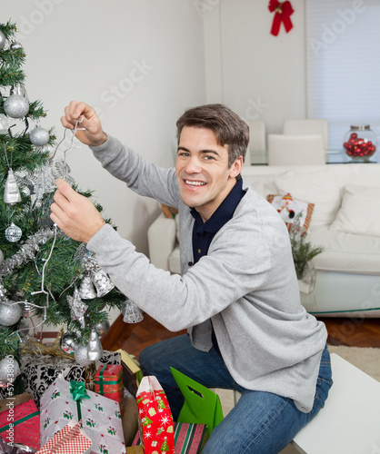 Happy Man Decorating Christmas Tree