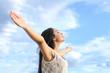 Beautiful arab woman breathing fresh air with raised arms