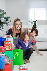 Mother With Children Sitting By Christmas Gifts