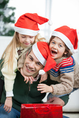 Father Piggybacking Children During Christmas