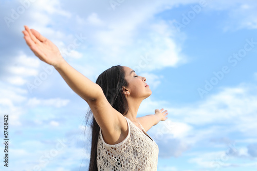 Beautiful arab woman breathing fresh air with raised arms
