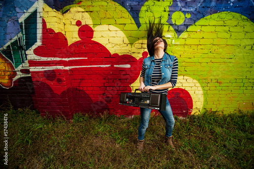 Girl dancing in front of graffiti with recorder