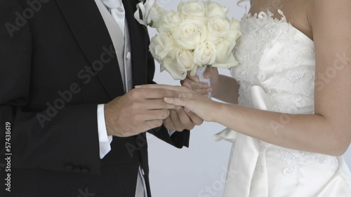 happy newlywed groom sliding wedding ring on brides finger