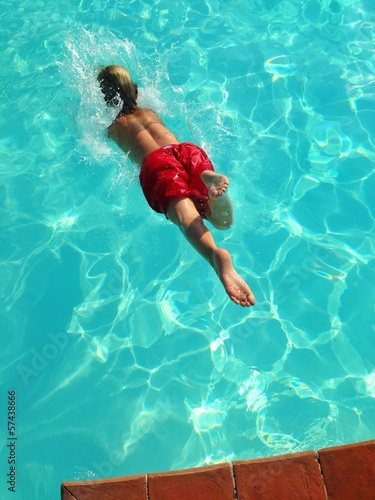 young boy diving in pool