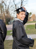 Student In Graduation Gown Holding Certificate On Campus