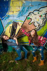 Two young girls with recorder in front of graffiti