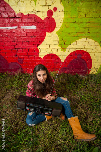 Young girl with recorder in front of graffiti