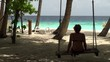 Girl swinging on a swing in the Maldives beach