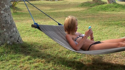 Girl in a hammock at the beach is viewing SMS on your mobile.
