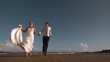 Cheerful bridal couple running on the beach