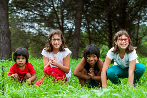 Cute girls sitting in green grass field.