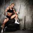 Beautiful muscular bodybuilder woman sitting on tyres