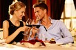 Beautiful young couple with glasses of red wine