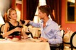 Young couple with bottle of red wine in luxury restaurant