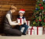 Mother and her lIttle boy in Santa hat with gift box