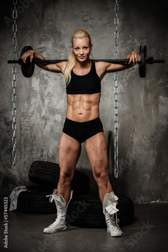 Beautiful muscular bodybuilder holding weights