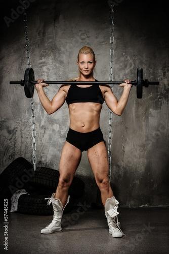 Beautiful muscular bodybuilder holding weights