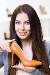 Portrait of woman keeping brown leather stylish shoe