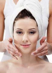 Makeup artist applies cosmetics on the woman's face