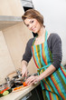 Woman in striped apron chops vegetables