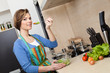 Beautiful woman in striped apron cooks in the modern kitchen