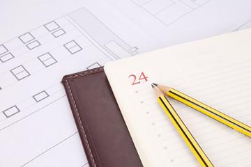planos de edificio con lápices y agenda