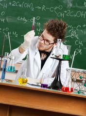 Mad professor examines a beaker in his laboratory