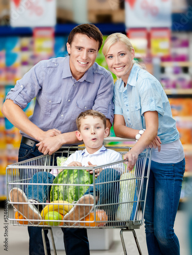 Family drives shopping trolley with food and son