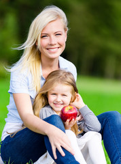 Mother and daughter with apple sitting on the grass