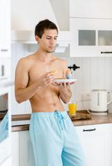 Half-naked man has breakfast at kitchen